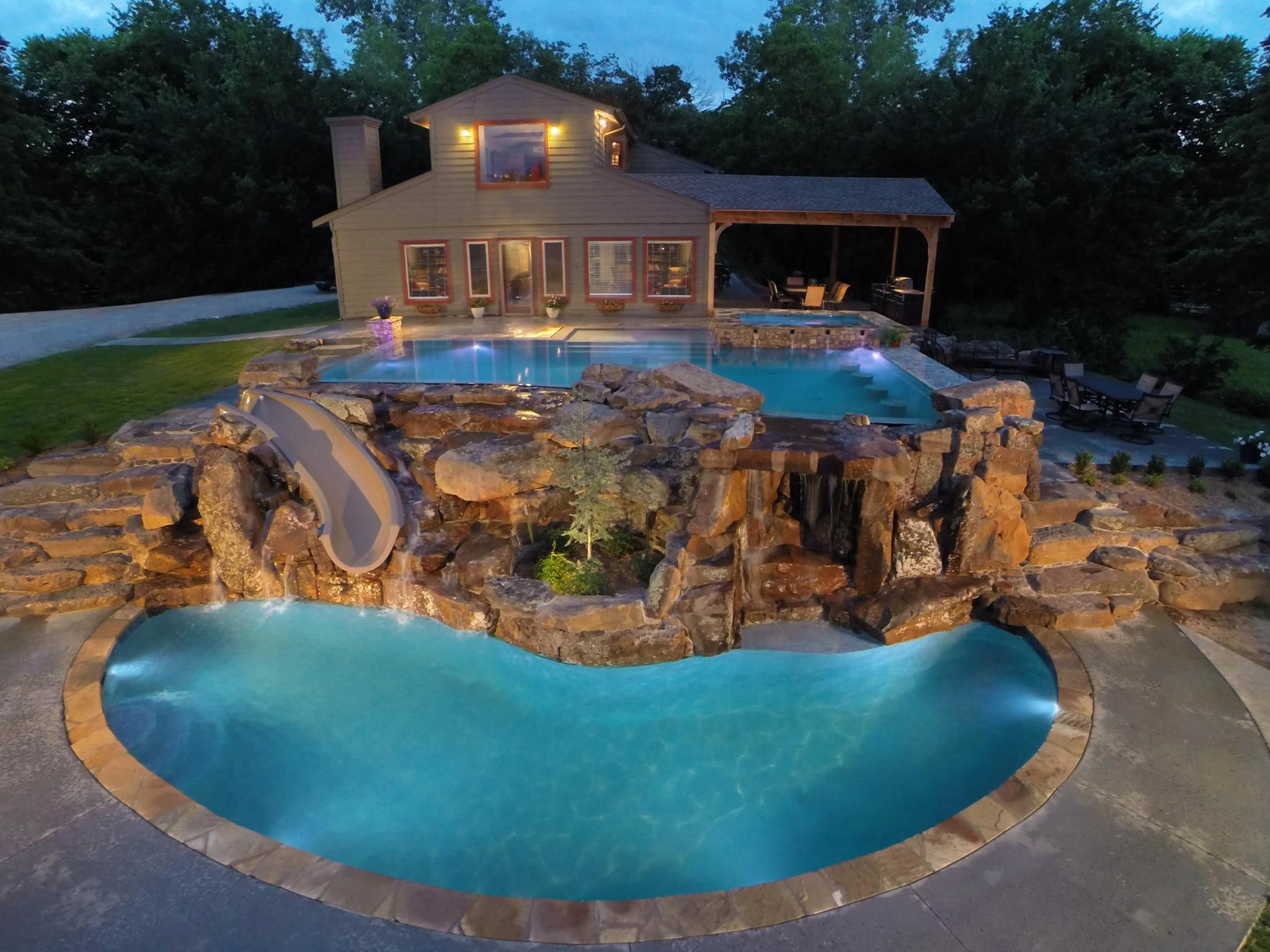 Two level luxury pool with waterfalls slide swim up bar for Luxury swimming pools