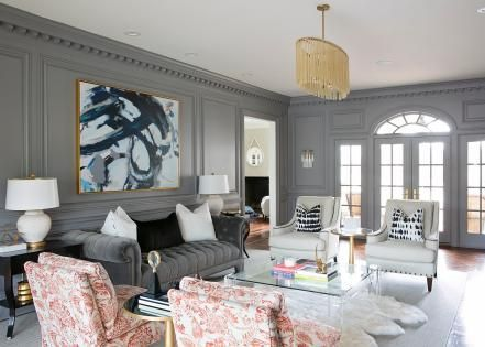 These transitional gray sitting rooms showcase an interesting blend of styles. One formal living room features a Chesterfield sofa and other comfortable furniture centered around a clear Lucite coffee table and large sheepskin rug. The second, more casual living space, includes comfortable furniture but places a stronger emphasis on art and modern furnishings.