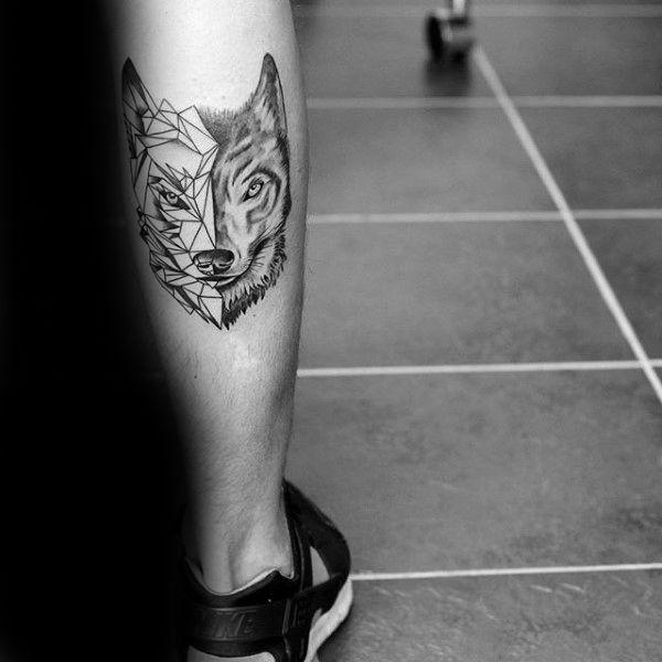 posterior de la pierna del becerro del hombre con el tatuaje de lobo