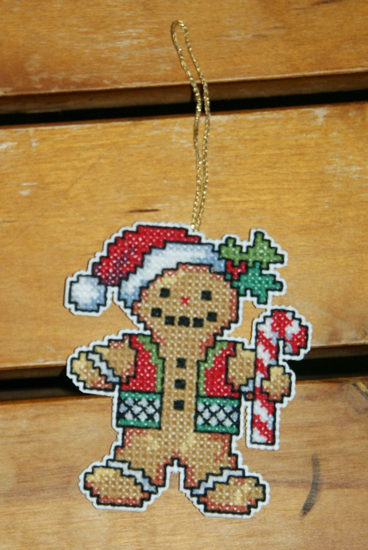 Dieses selbstgestickte Ornament ist ideal für die Weihnachtsdekoration bei Euch zu Hause oder auch zum Verschenken! Auch super am Weihnachtsbaum!  Gestickt auf weißem Plastic Canvas. Ein Pfefferkuchenmann im witzigen Format! An einem goldfarbenen Aufhänger!  Größe ca. 7,5 x 6,5 cm an den weitesten Stellen.