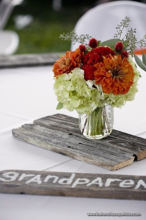 Rustic barn floral centerpiece in mason jar on wooden
