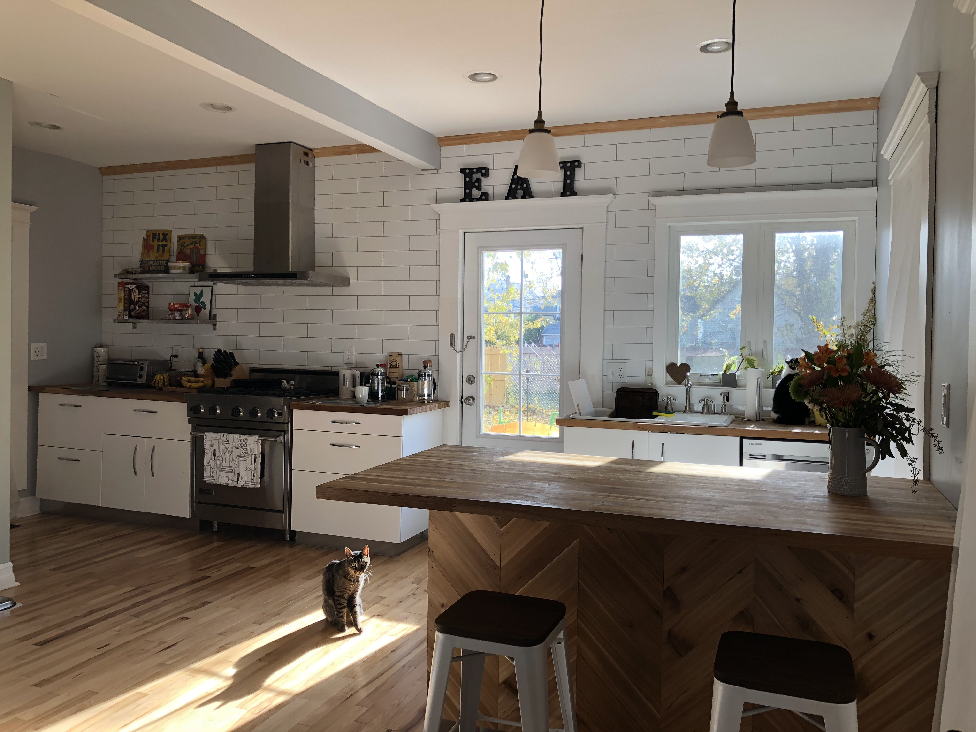 Longer white tile backsplash installed from the