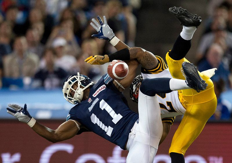 Toronto Argonauts wide receiver Dontrelle Inman (11) has a pass broken up by Hamilton Tiger-Cats defensive back Arthur Hobbs during the first half of a Canadian Football League game in Toronto, Ontario, Friday, Oct. 4, 2013. (AP Photo/The Canadian Press, Frank Gunn)