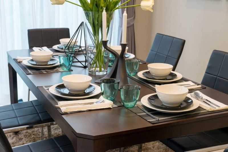 Dark Wood Dining Room Table With Six Place Settings Comfortable Modern Chairs And Large Central Vase Of Flowers