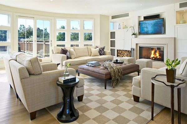 Living Room layout with large center ottoman and fireplace/TV focal point  alongside expansive windows