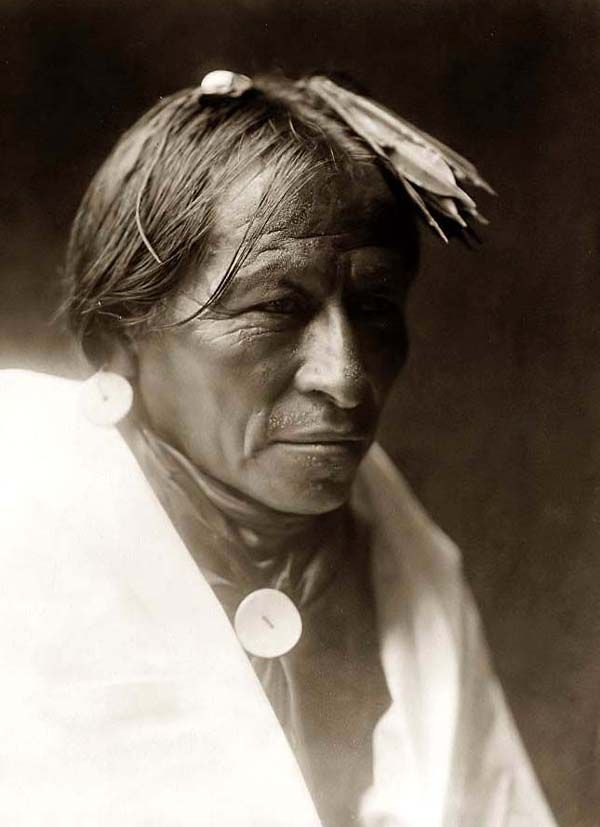 Here we present a rare image of a Taos Indian Brave. It was taken in 1905 by Edward S. Curtis.    The image shows a Head-and-shoulders portrait of the man facing slightly right.The man has several feathers in his hair    We have created this collection of images primarily to serve as an easy to access educational tool. Contact curator@old-picture.com.