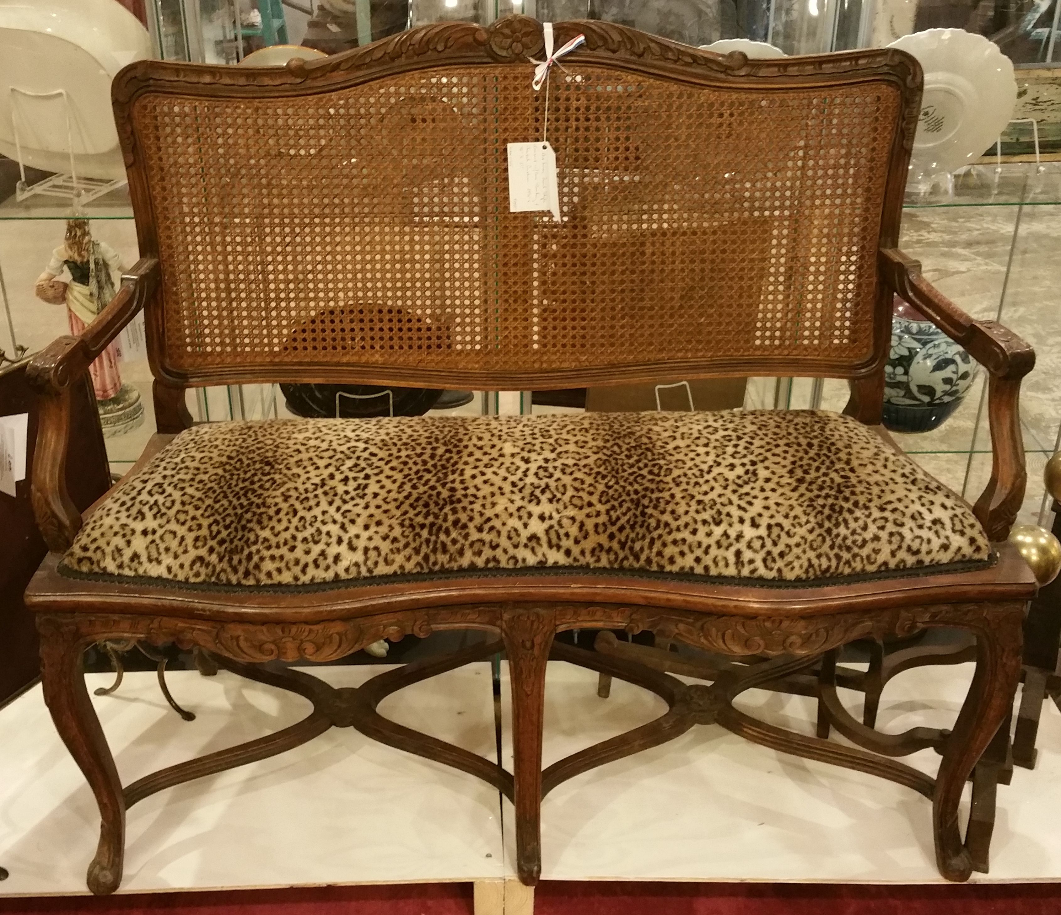 "From b407, An Unusual French Style Loveseat with Cane Backing and a Cheetah Cushion, (39"" x 46"" x 21"") $1750.00"
