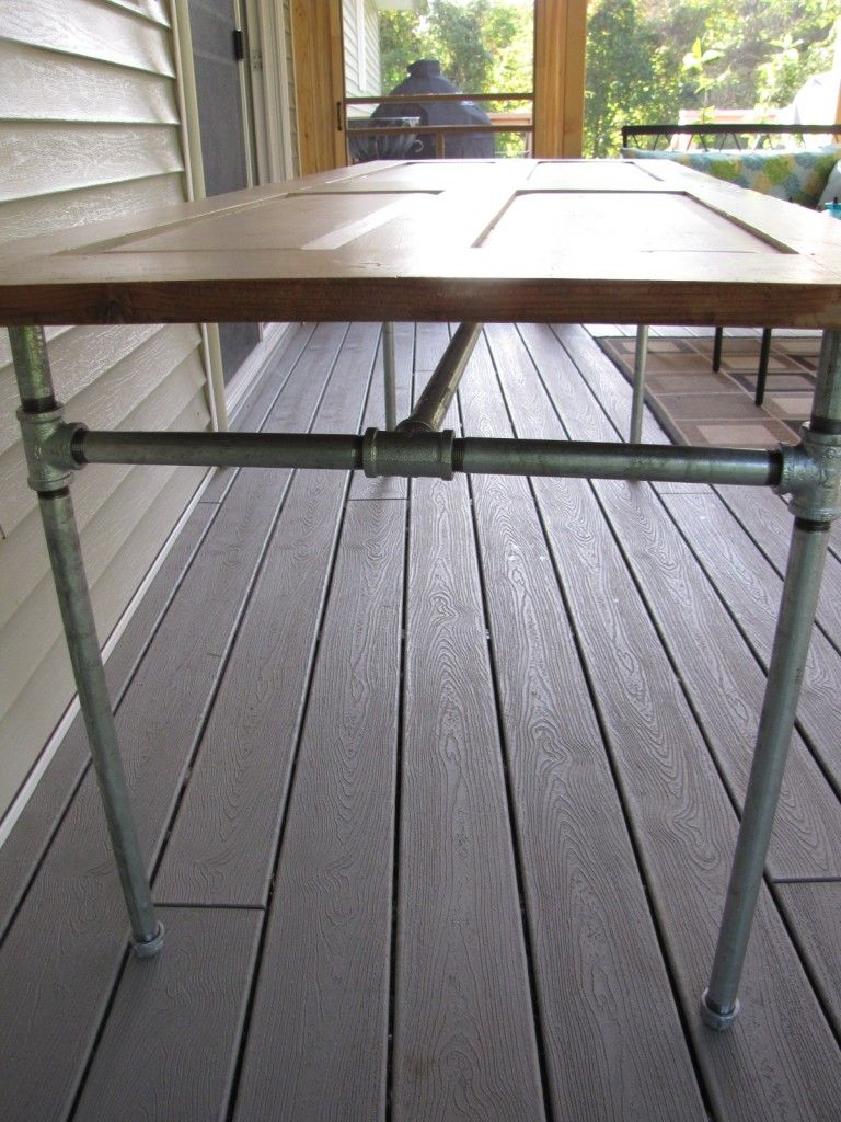 Diy table made from an old door and galvanized pipe repurposed