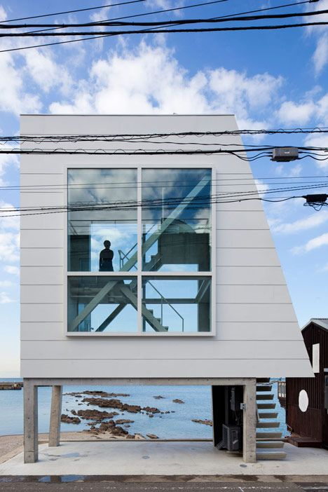 This tiny seaside home in Kanagawa by Japanese office Yasutaka Yoshimura Architects is contained within little more than a pair of oversized windows raised up on stilts
