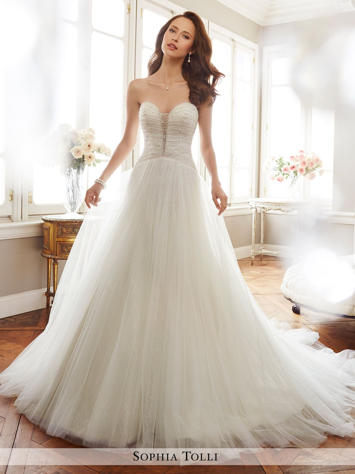 6b30ab7f75 Strapless misty tulle A-line gown with soft allover lace set underneath  tulle layers features a semi-sheer plunging sweetheart neckline