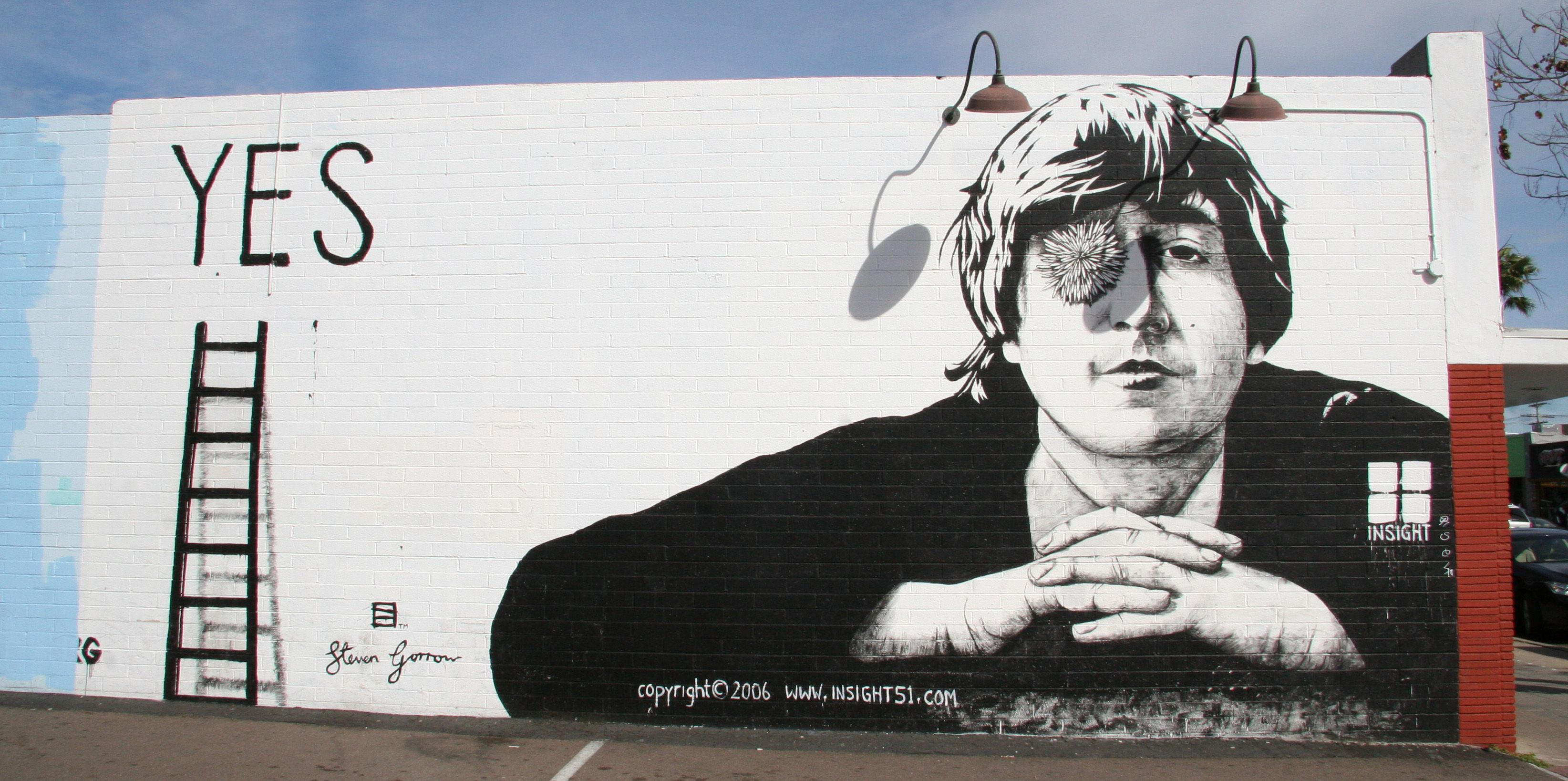 Wall art of john lennon located one driveway east of cass street on