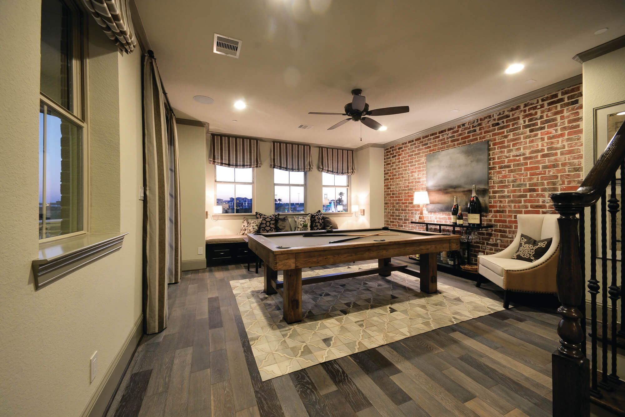 The game room is accented by a brick wall creating a warm touch