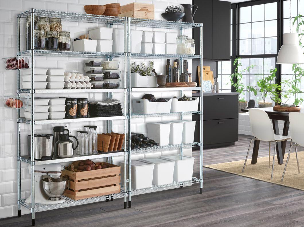 Dos estanterías galvanizadas en una pared blanca con una cocina en gris oscuro detrás.