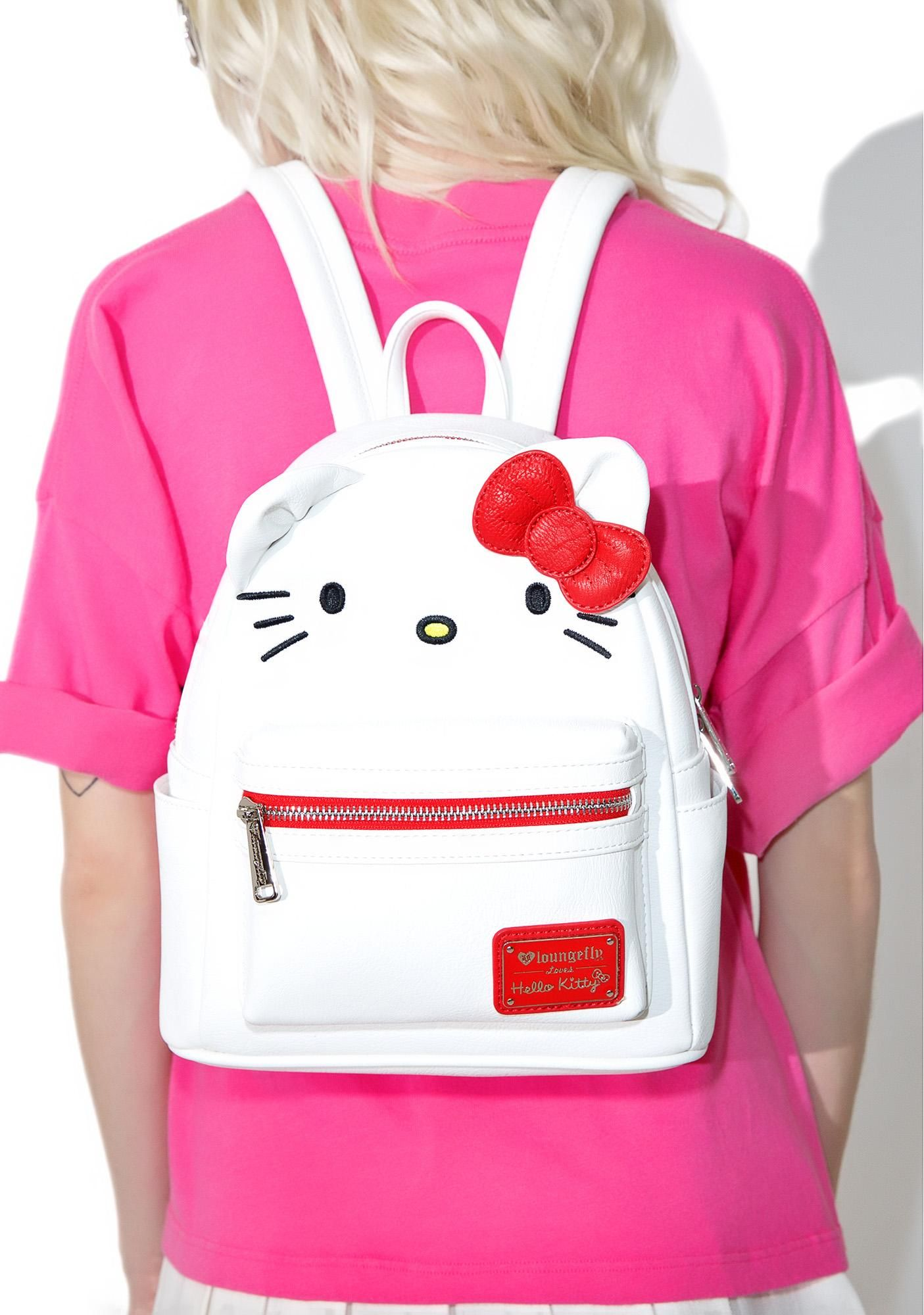 Loungefly X Hello Kitty Mini Backpack cuz yer BFF alwayz has yer back, bb. This supa cute vegan leather mini backpack is in the design of Hello Kitty with a 3D bow and ears applique,roomy medium interior, front zip pocket, two side pockets, multicolor adjustable straps, and locker loop detail.