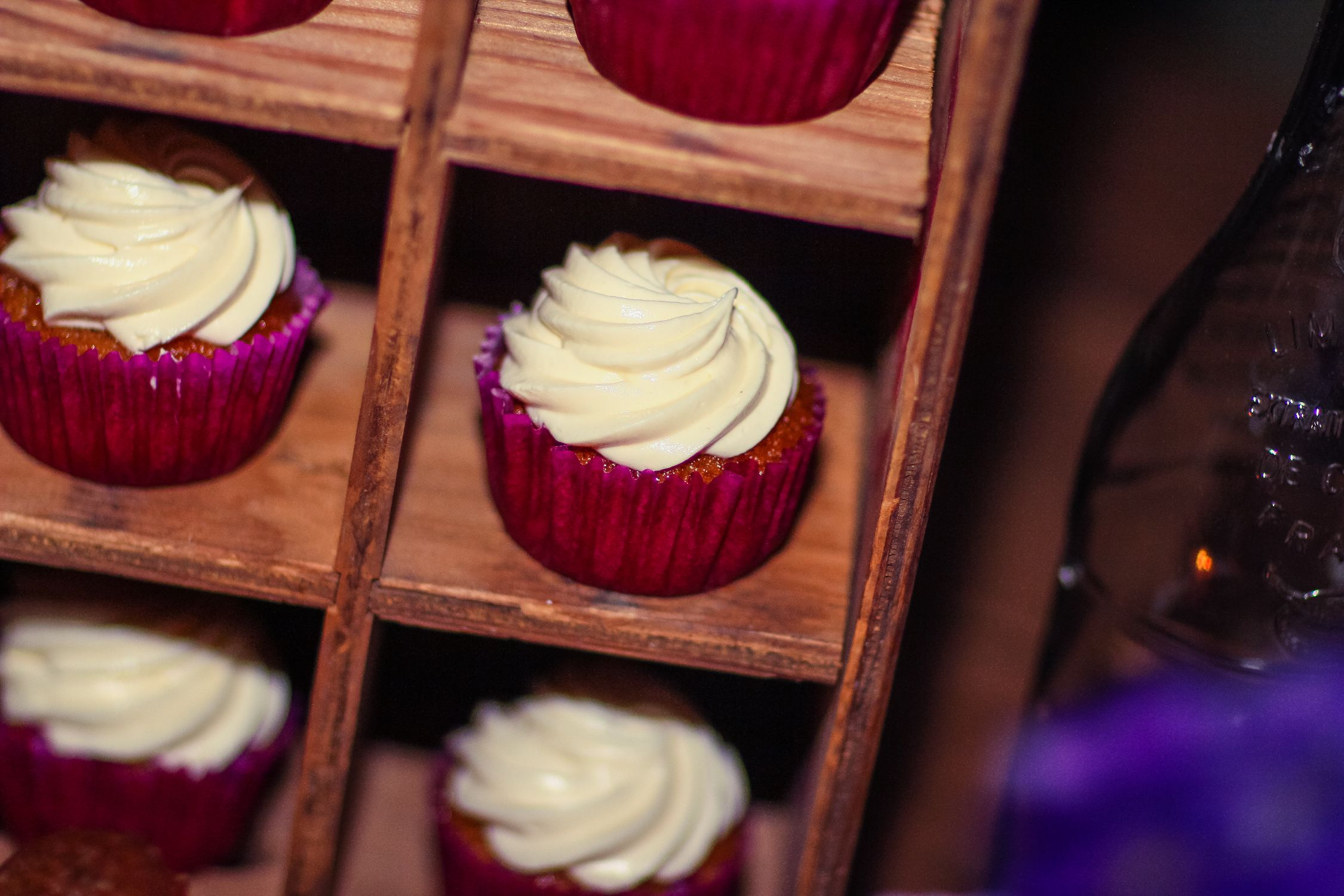 Best way in the world to display cupcakes... this is a milk bottle crate turned on end.     Purple wedding, birds, birdcages, dessert bar wedding.    Desserts by: Sugar and Spice Specialty Desserts Photographer: Amy Atkins Photography Villa Florentina Wedding Catrina Marie Designs