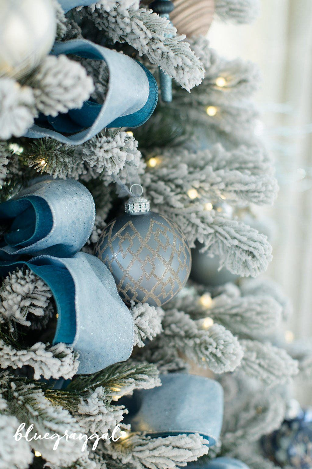 Peacock Blue Ribbon On A Pre Lit Artificial Flocked Tree With Blue And Gray O Blue Christmas Tree Decorations Blue Christmas Decor Silver Christmas Decorations