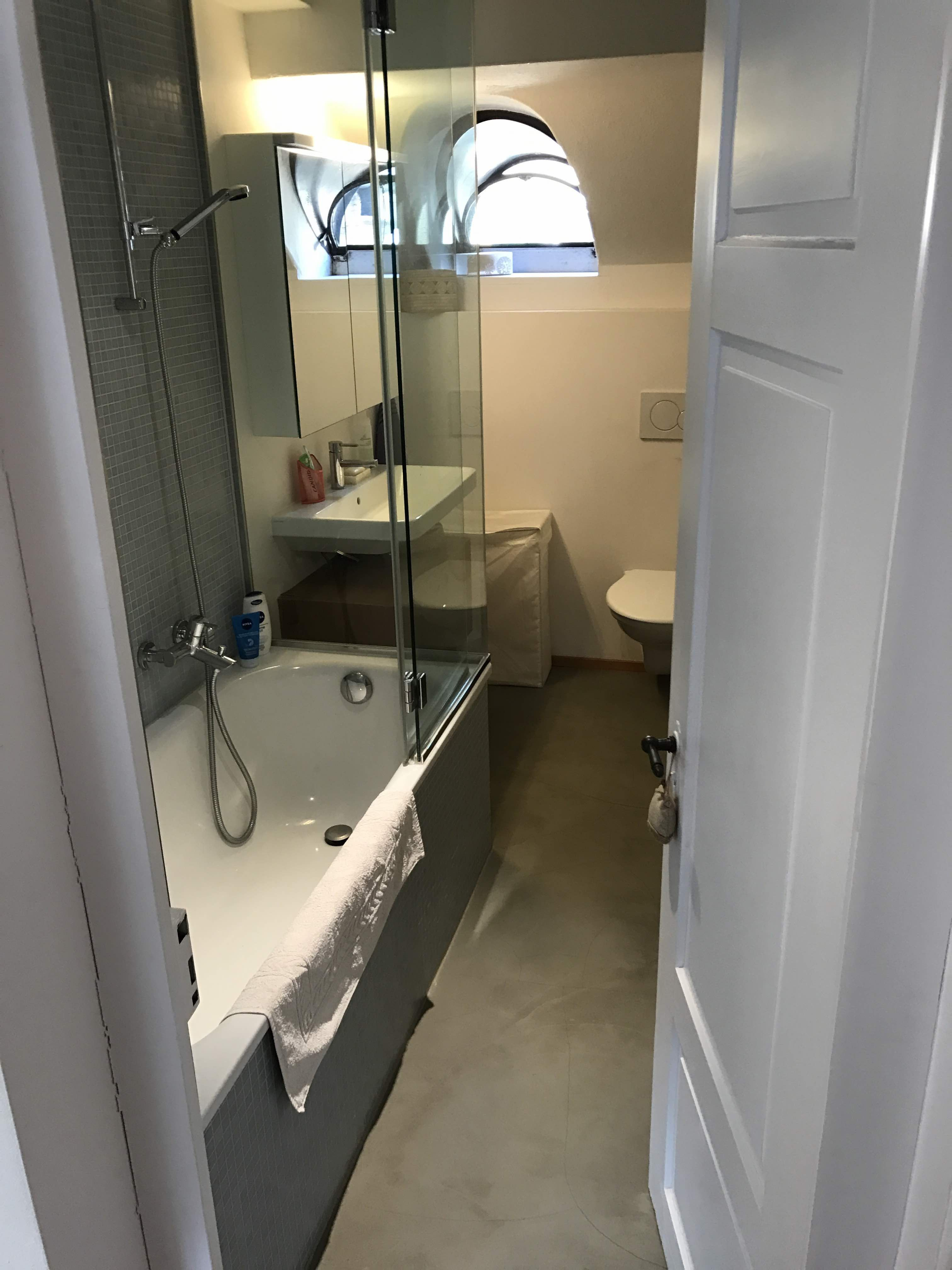 Modernes Bad mit Badewanne und Dusche, WC und Catalano Keramik, Eichenholz und als Kontrast ein Gussboden.