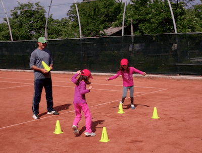 Instructor or coach teaching child how to play tennis on a court.
