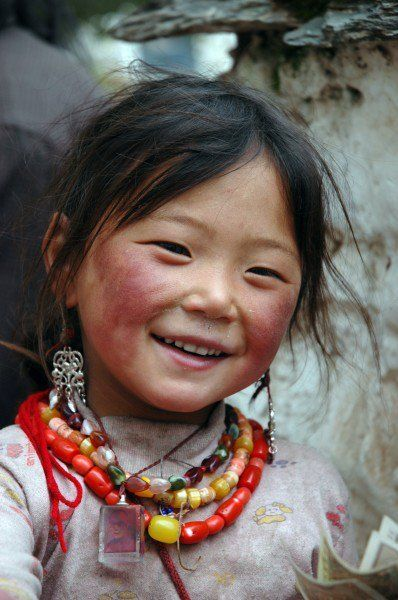 Portrait Photography Inspiration : Rosy-Cheeked Tibetan Child Wearing Necklaces Sweet Smile & Rosy Chapped Che