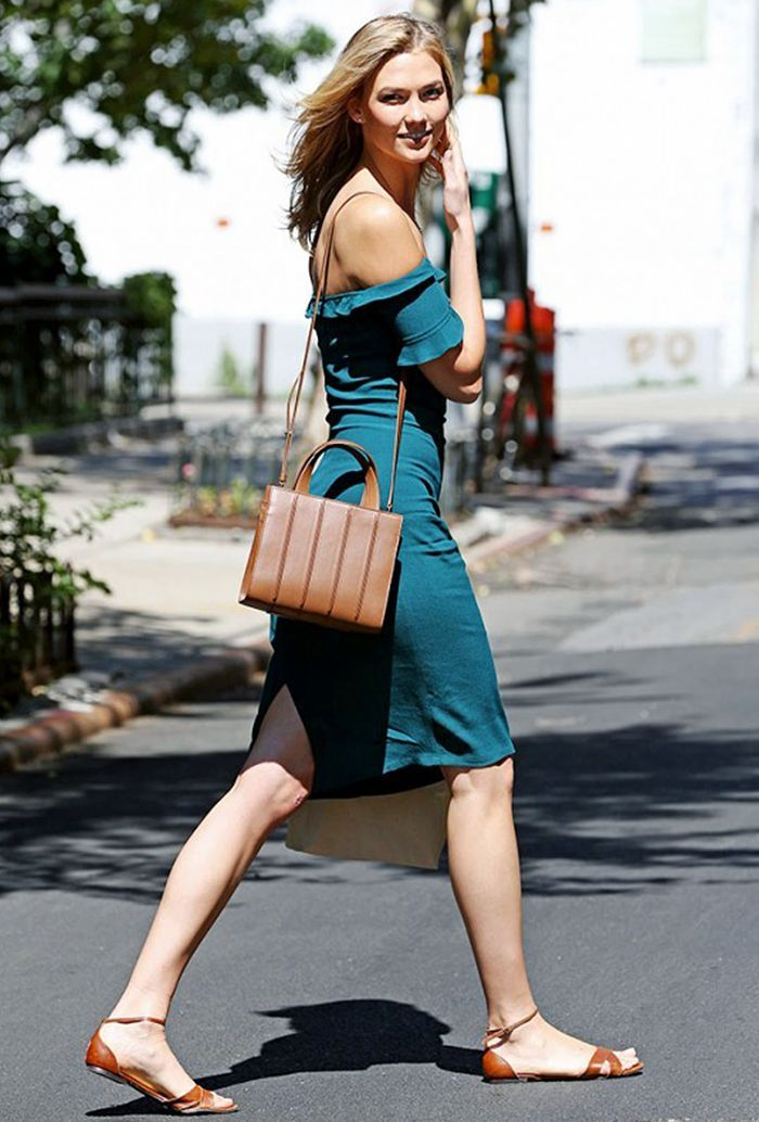 Karlie Kloss wears a teal off-the-shoulder dress with brown sandals and a brown crossbody bag