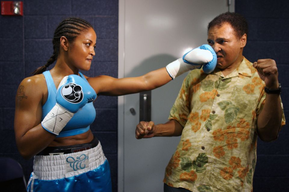 Ali takes a punch from his daughter Laila Ali while sparring before her  fight against Erin Toughill in Laila retired from her own successful boxing  career ...