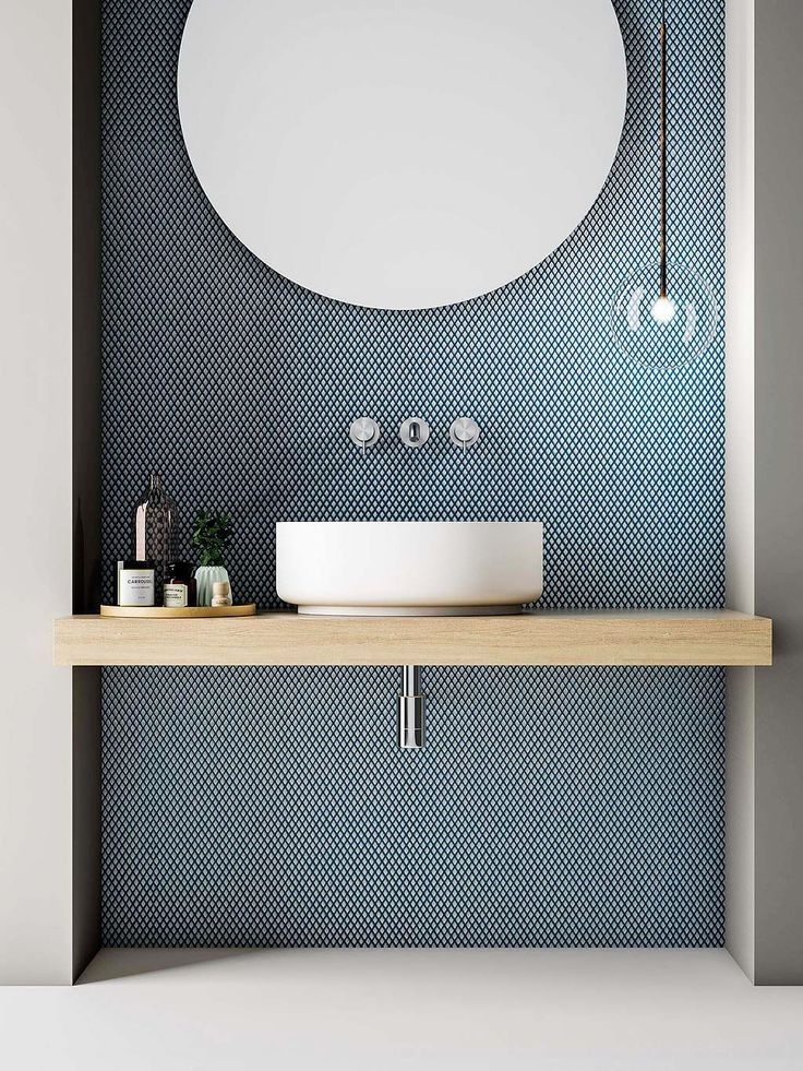 Love the tile with the circular mirror and pale wooden vanity. Clear, single globe light and cute tray of bathroom essentials. Very crisp. #homedecor #simplebathroomdesigns