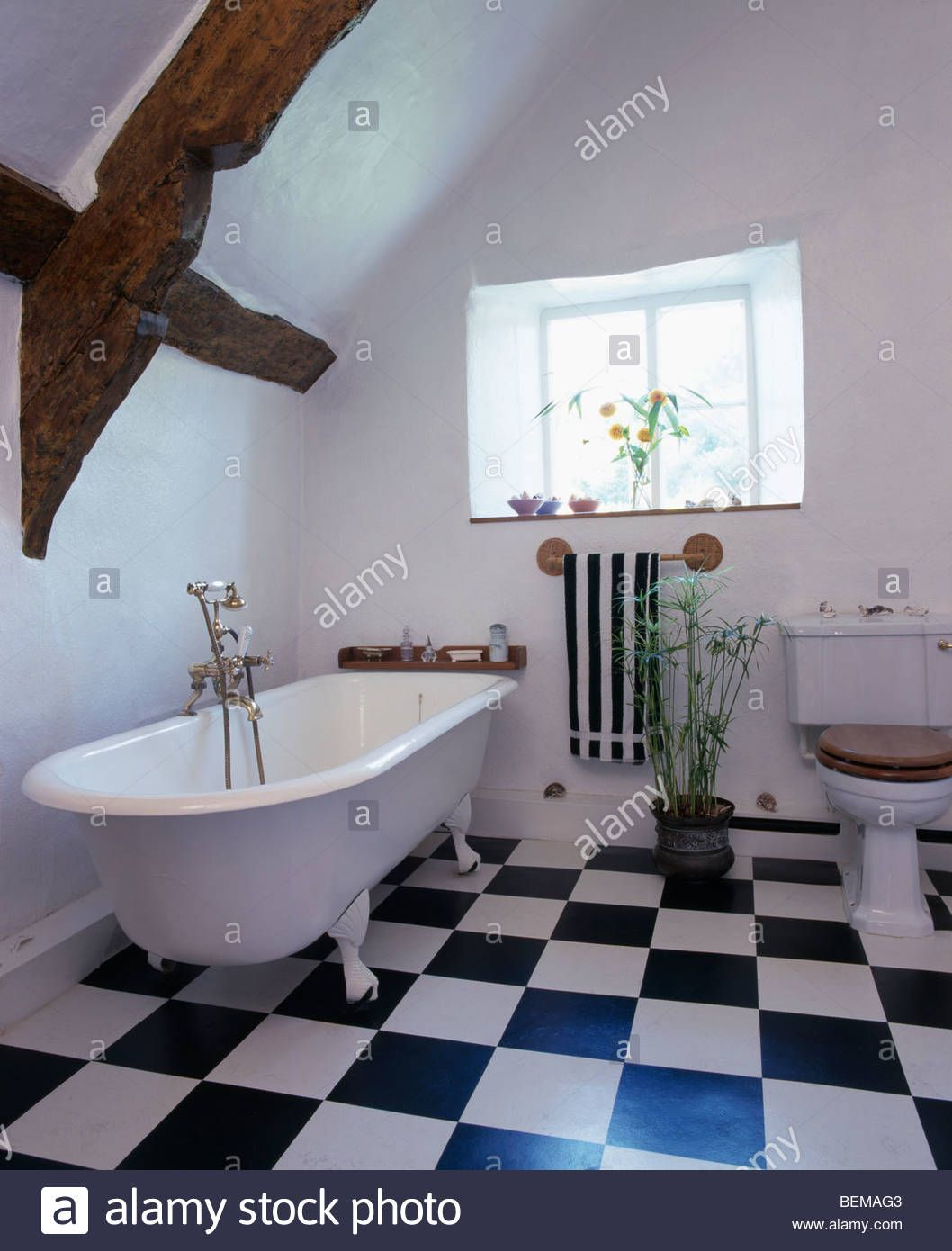 Rolltop bath and black+white chequerboard vinyl flooring