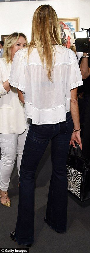 Elle Macpherson flaunts her sculptured figure in a sheer white top
