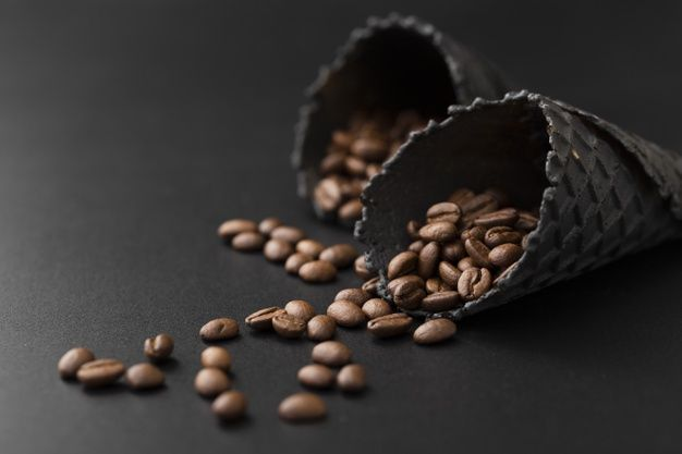 Dark cones with coffee beans on a dark t  Premium Photo