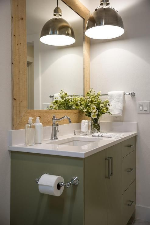 Lovely white and green cottage bathroom features a green washstand