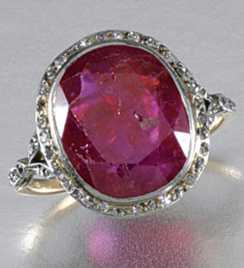 AN ART DECO RUBY AND DIAMOND RING, EARLY 20TH CENTURY. Collet-set with an oval ruby within a border of single-cut diamonds to similarly-set stylised foliate shoulders.