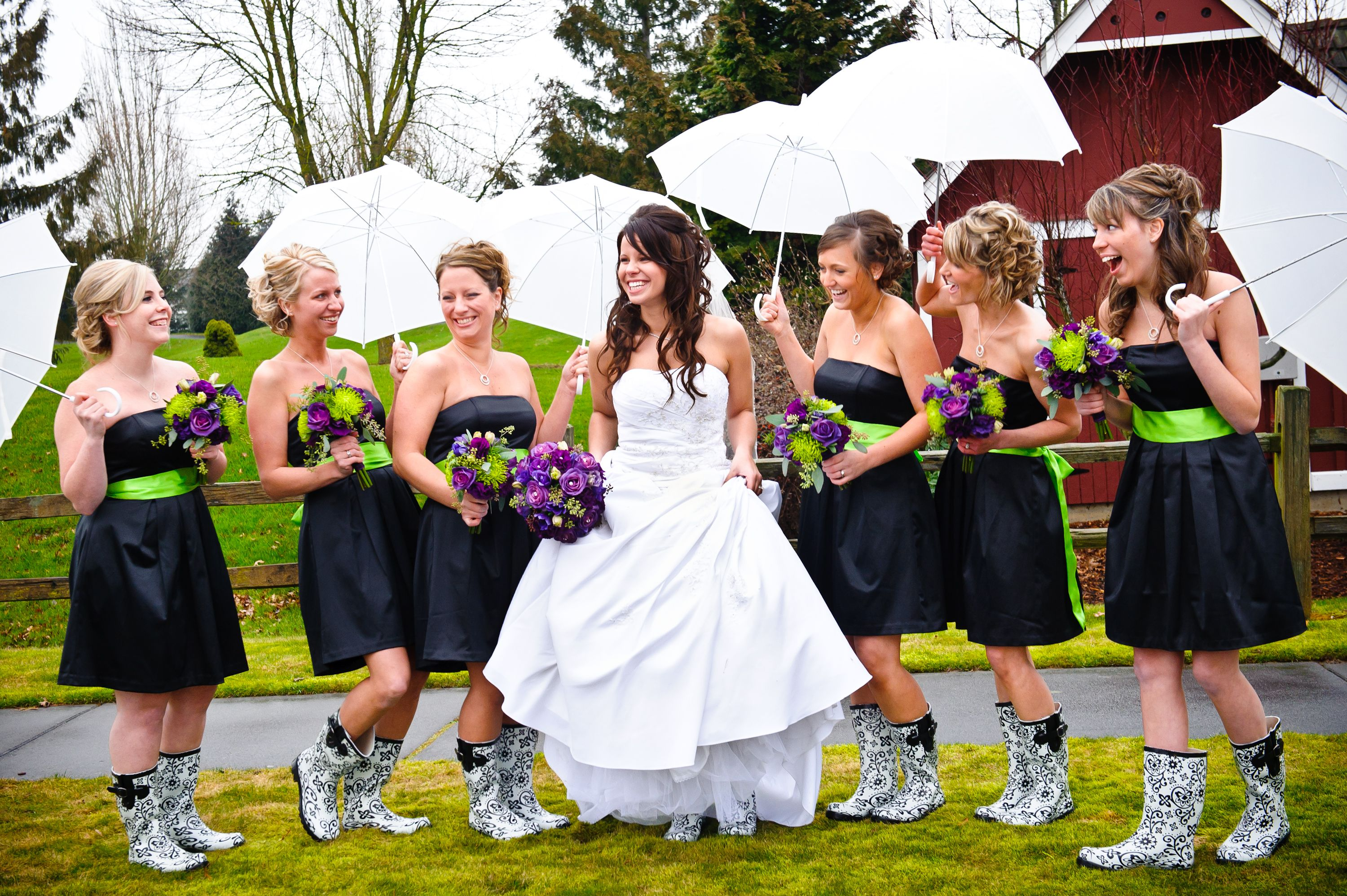 Matching bridesmaids' rain boots and umbrellas are perfect for the rainy weather.