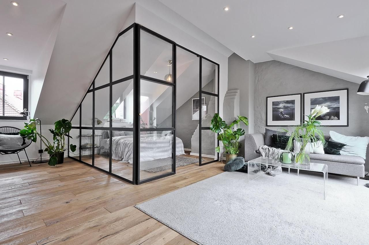 Attic apartment with industrial glass walls to