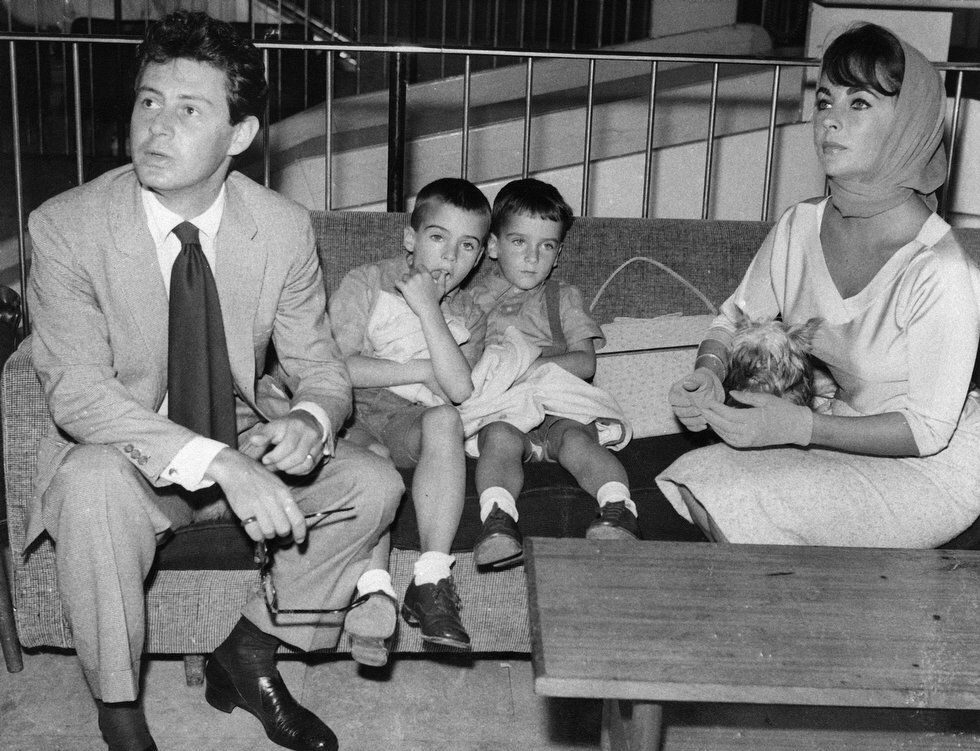 Actress Elizabeth Taylor and her husband Eddie Fisher wait for a plane at London Airport, Sept. 7, 1959, on their way to Paris. Ms. Taylor's two sons, Michael and Christopher Wilding are seated at center.