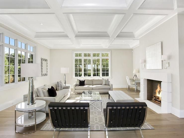 Contemporary living room features a coffered ceiling over a pair of natural linen sofas and a