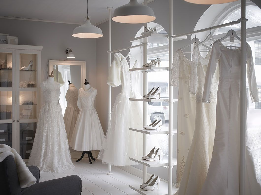 A Wedding Shop With White Display Shelves And Glass Door