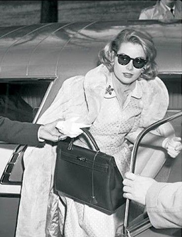 Grace Kelly and the famous Hermès 'Kelly' bag. Check out the hands ready to help her with any movement whatsoever.