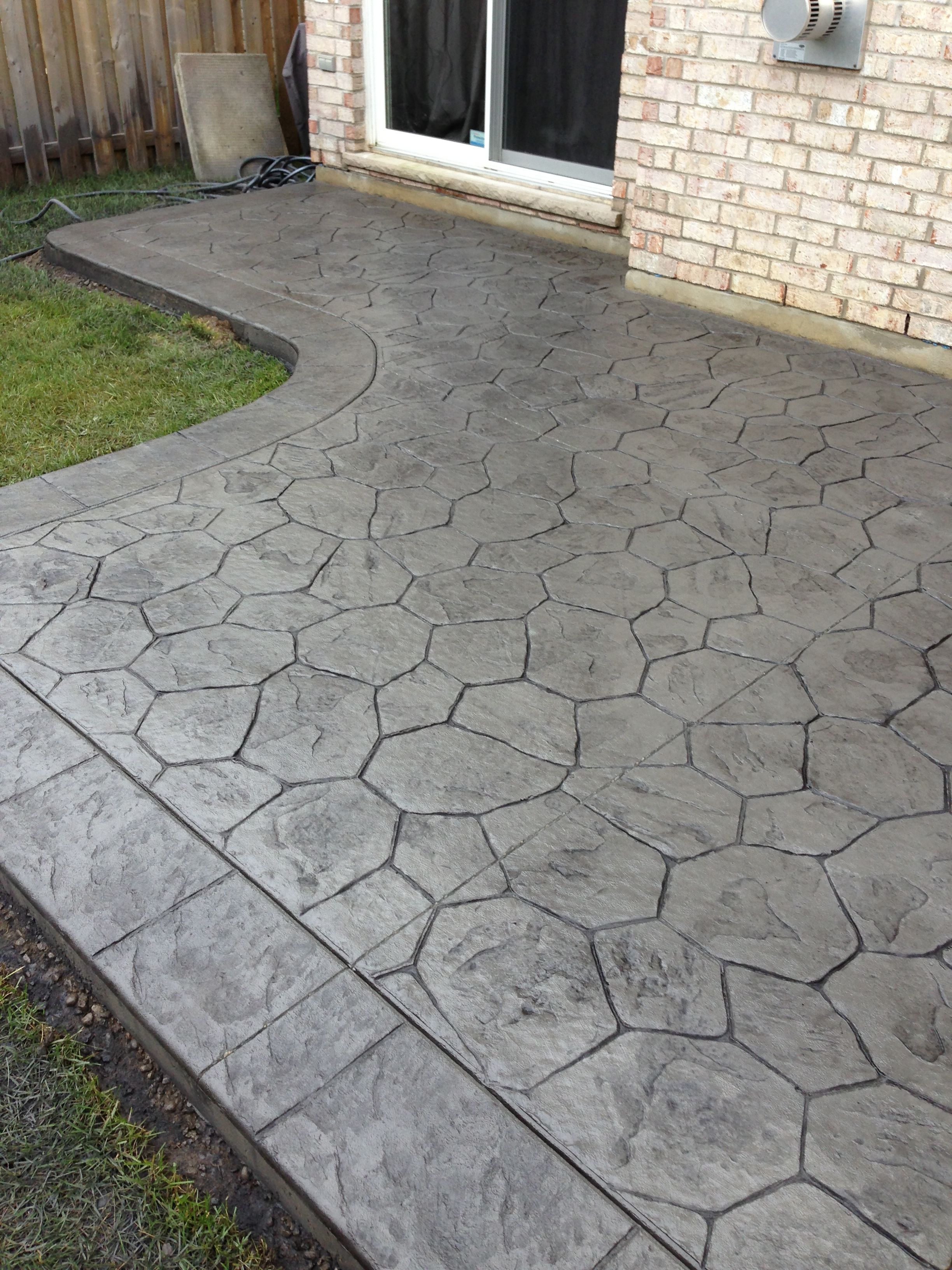 Random Stone Stamped Concrete Patio With Stone Block Border In