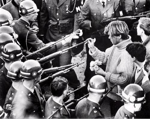 The essence of 'flower-power'. Putting a daisy into a gun barrel. A highly iconic photo of the era.