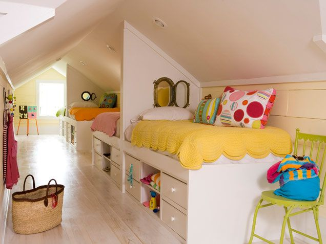 Four captain beds with bold bedding maximize and brighten this narrow attic space.