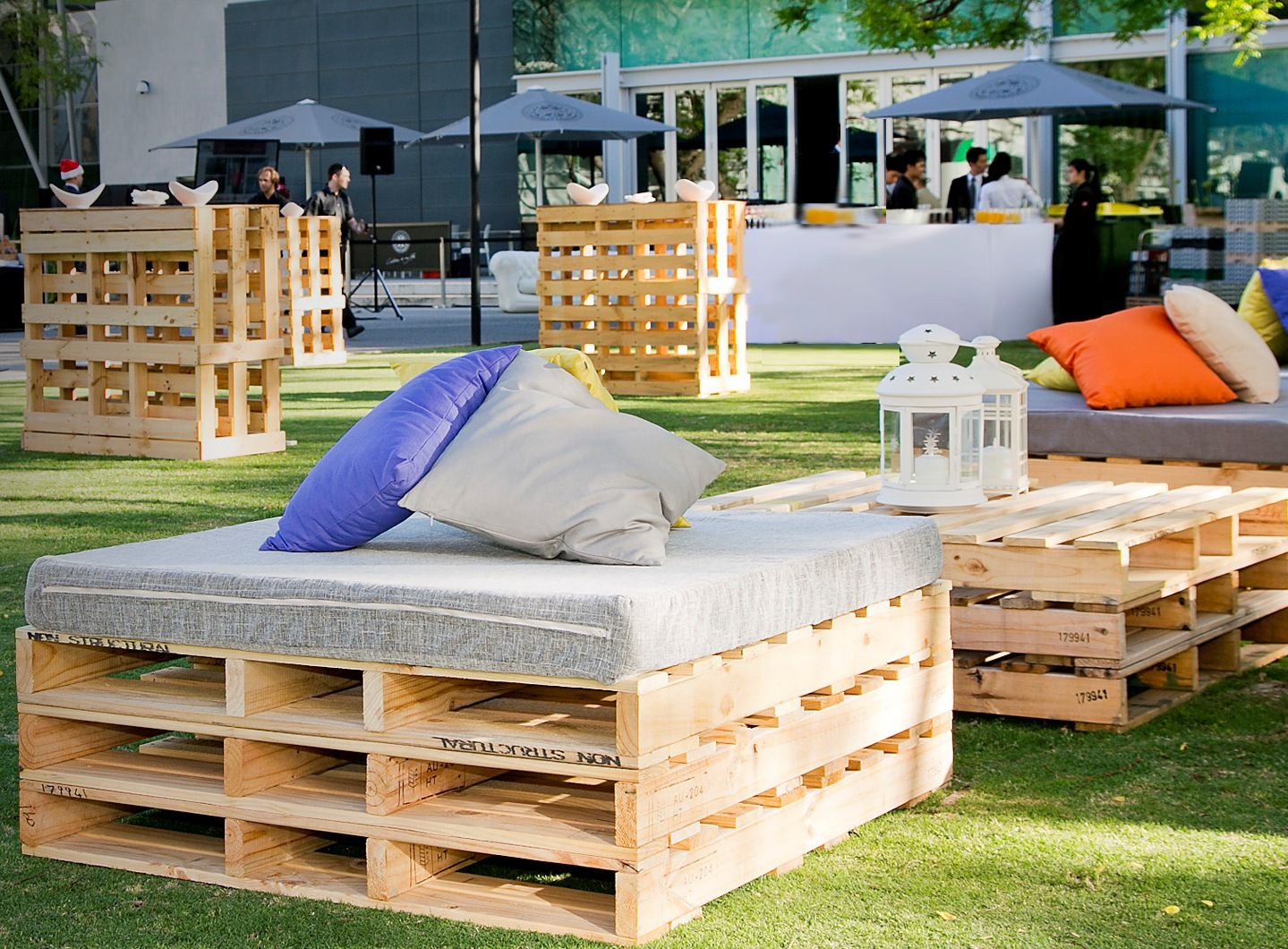 Rustic pallet seats with padded top and scattered cushions are the perfect element to hire for your next party
