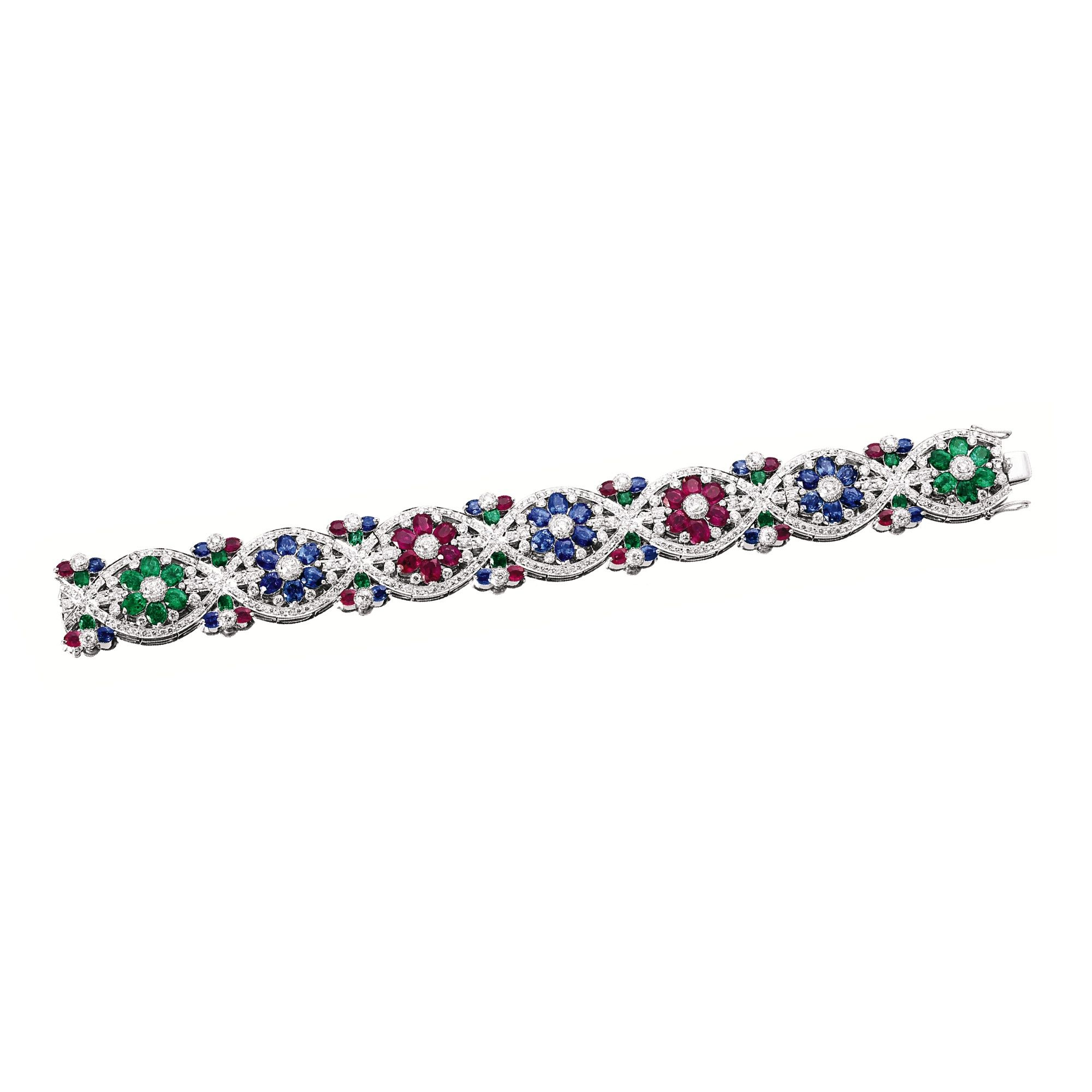 GEM-SET AND DIAMOND BRACELET The articulated strap composed of seven navette-shaped motifs, each centring on a brilliant-cut diamond, surrounded by oval emeralds, rubies and sapphires, embellished by circular-cut diamonds, the emeralds, rubies, sapphires and diamonds weighing 3.00, 4.20, 6.00 and 3.00 carats respectively, mounted in 18 karat white gold.