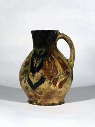 1226-1275. Pottery; rounded zoomorphic jug(fragment); yellow, brown and green glaze; handle of oval section with 2 applied strips at the top; body with panels each containing a dragon; highly decorated style.