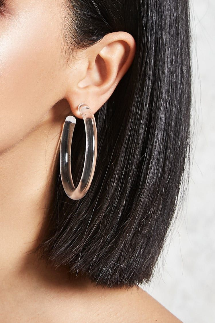 41382668d157 A pair of clear acrylic hoop earrings featuring a post-back closure ...