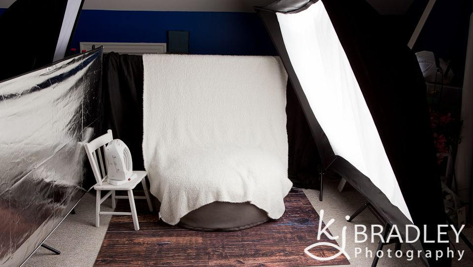 Newborn photography studio lighting setup with softbox and reflector