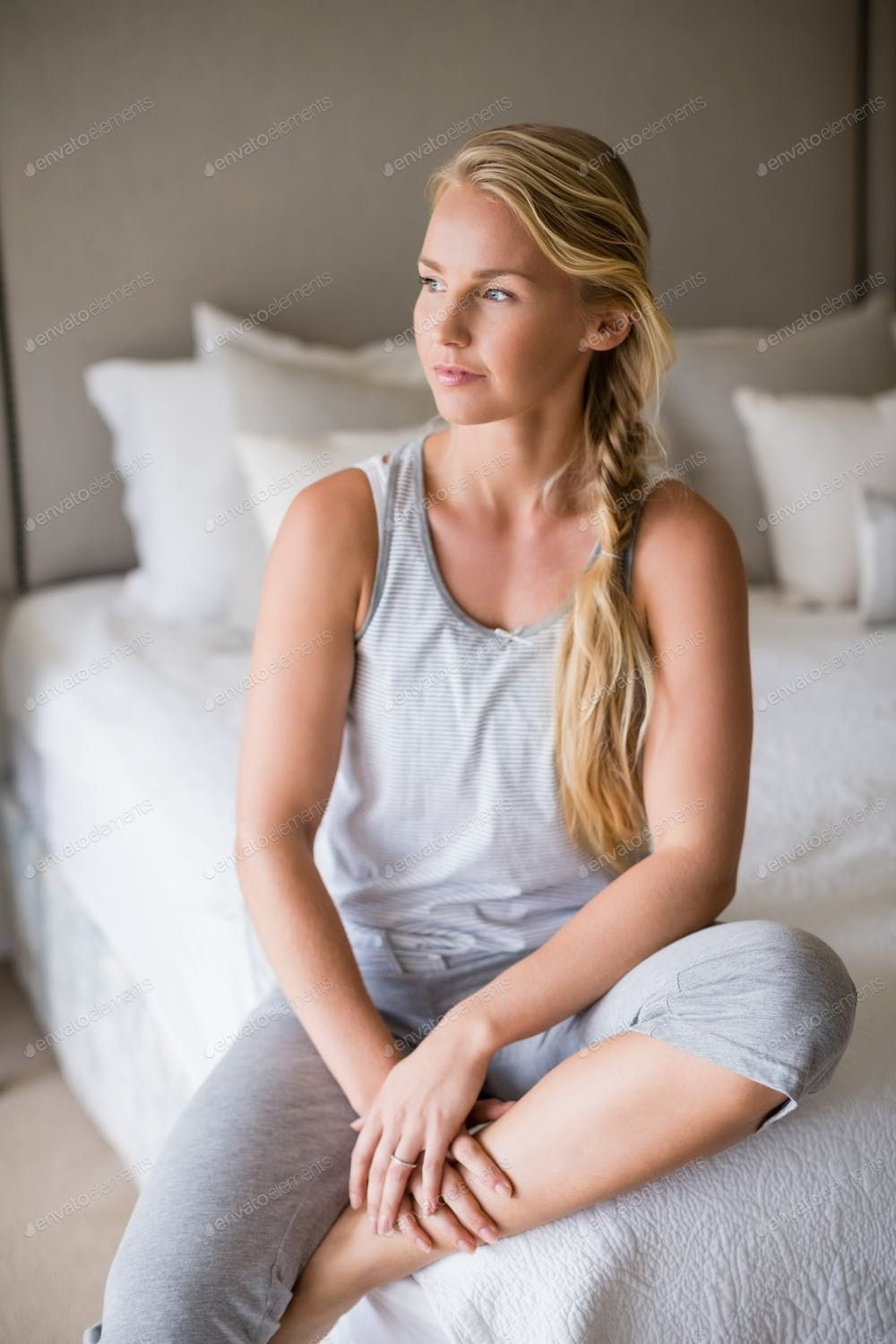 Thoughtful Beautiful Woman Sitting On Bed In Bedroom By