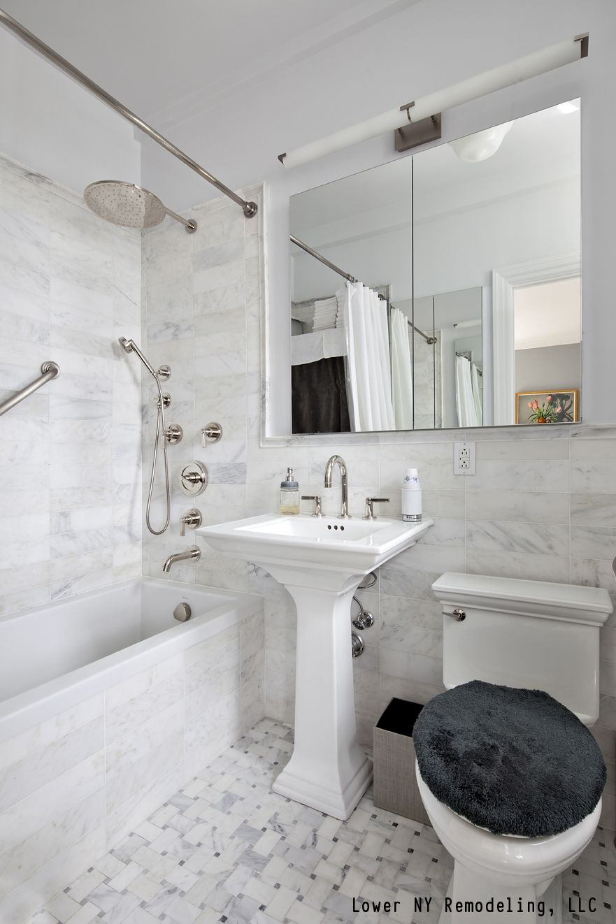 A contemporary bathroom with white tile, a pedestal sink and a rain ...