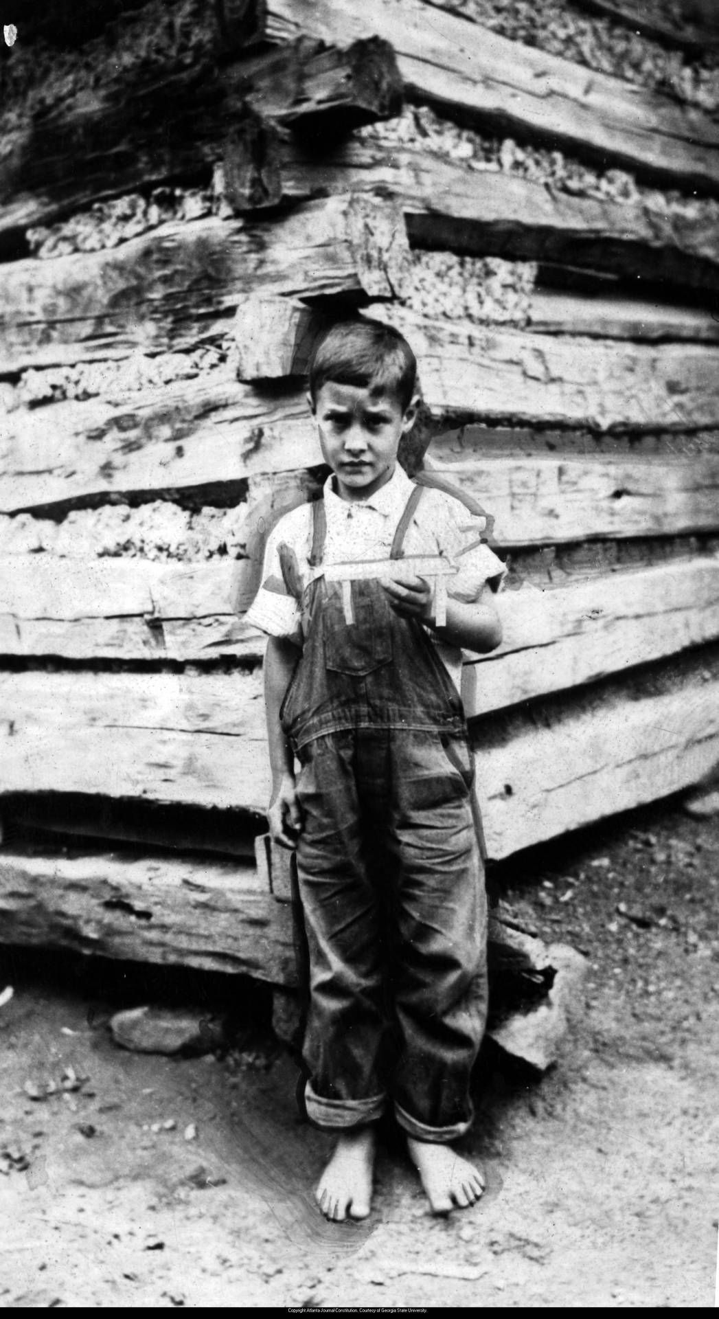 Barefoot young boy (Paul Wooten) outside log cabin, holding a toy he has whittled, Georgia, December 25, 1938.