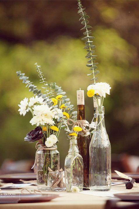 Garrafas e potes de vidro dão um ar rústico a decoração do seu casamento, combinados com flores!