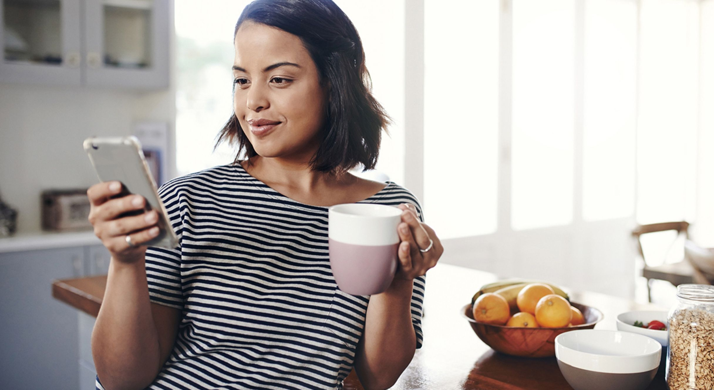 Woman looking at her phone holding a cup of tea